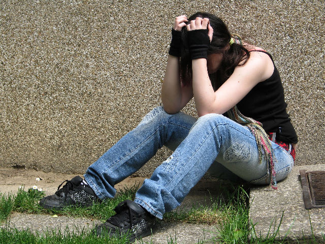 Young woman sits on the floor outside her flat, looking depressed